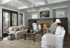Ashley Goforth    Craftsman style home design with coffered ceiling, coffee stained built-ins flanking brick fireplace, gray walls paint color, flatscreen tv, Asian coffee table, gold & blue rug, white jars, white slip-covered sofa and sand linen slip-covered chairs.