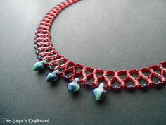 This adorable beaded collar features a juicy palette of cherry red, hot pink, and intense blue that is perfect for summer.  The collar is woven with a curved variation of chevron chain, and features a