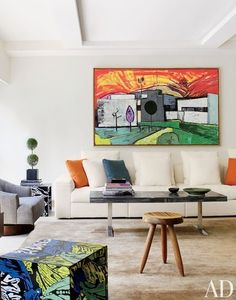 In the living room of a Manhattan apartment designed by Mica Ertegun, a Martin Kippenberger painting overlooks a Poliform sofa covered in an F. J. Hakimian cotton, a vintage marble-and-chrome cocktail table, and a Charlotte Perriand stool   archdigest.com