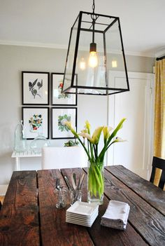 gray walls for dining room. different main chairs vs. side chairs. rustic table. yellow and green accents.  white accent table