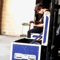 so this is harry. in a tank top. playing his guitar. you're welcome.