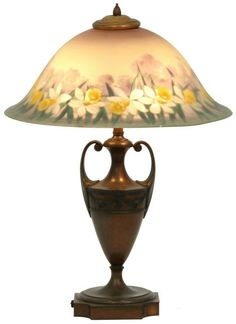"""17.5 in. dia. Copley style reverse painted shade with a border of beautiful daffodils, leaves and silhouetted trees in the background; signed """"The Pairpoint Corp"""". On a brass 2 handled urn base with relief floral garland highlights."""