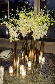 Cluster tall, narrow metallic vases of Dendrobium orchids with flickering votive candles for a chic evening reception.