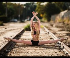 flexible girl with long legs spanning the width of train tracks