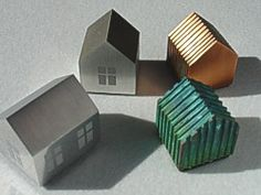 Love these little house paperweights from Finnish metal workers  Latimeria.  They are so sweet I would love to have a little cluster of them on a bookshelf!
