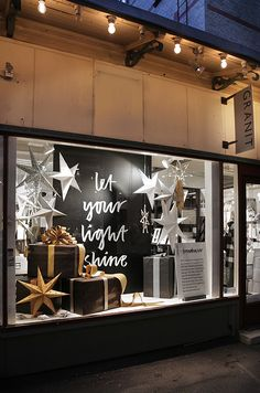 Black, white, silver and gold holiday window display with stars and wrapped presents. Festive fun!