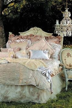 Beautiful bedded with a carved headboard ruffled tulle bedskirt and loaded with pillows. A chandelier is conveniently hanging in a nearby tree. Shabby cottage and romantic