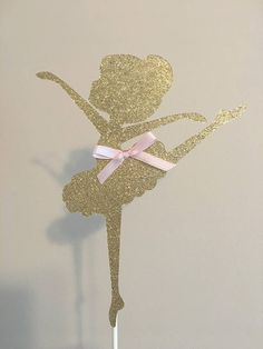 Gold Glitter Ballerina Cake Topper. Great for ballerina birthday parties or baby showers. Made from gold glitter card stock and pink satin ribbon. Measures 8 tall. Colors and ribbon color can be changed to your choice or without ribbon. Front facing only, back is plain white