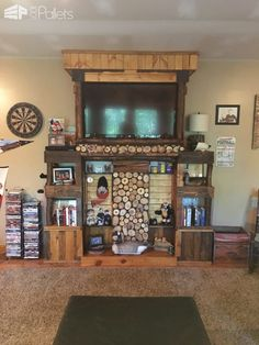#LivingRoom, #PalletEntertainmentCenter, #PalletTvStand, #PalletWall, #RecycledPalletShelves, #Rustic Here's my Pallet and Log Entertainment Center. I built this in my basement to go along with the pallet wall, fireplace mantle and barn-style doors that I also made from pallets.  This outstanding Pallet and Log Entertainment Center is an