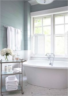 Linda McDougald Design | Pretty blue wall paneling and an awesome bath tub with a cart. In love.