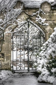 .Charming iron gate of a stone house in the snow