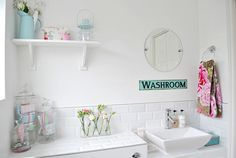 white bathroom with blue accents; open shelving; washroom