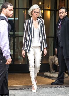 Stylish studs: Cara Delevingne, 24, was spotted in a pair of white skinny trousers studded with gold buttons as she stepped out in New York on Wednesday