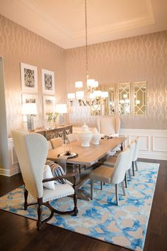 A shimmering blue and beige rug pops in this glamorous, neutral and transitional dining room. Wallpaper with a metallic pattern provides a sleek backdrop for artfully hung mirrors. A mix of seating blends with a rustic-casual table for a cozy, relaxed vibe.