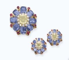 A MULTI-COLOURED SAPPHIRE FLORAL SET, BY MAUBOUSSIN. Comprising a brooch and a pair of ear clips, each designed as a cushion-shaped yellow sapphire pistil within a brilliant-cut diamond surround to the cushion-shaped sapphire petals with ruby collet detail, circa 1945