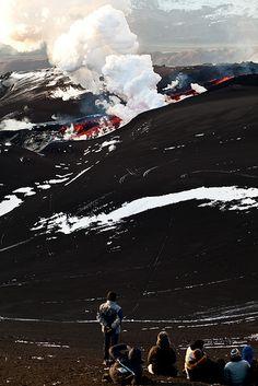 Spectators watch lava slowly crawl across the barren landscape.   Some folks say God is dead - http://www.sashaslavic.com/