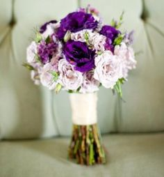 bouquets of lavender spray roses, purple ranunculus and purple anemones wrapped in slate grey ribbon.