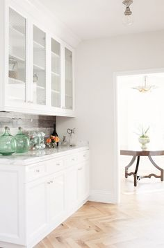 All white kitchen (or maybe just the butler's pantry cabinet). Hardwood floors in a chevron pattern.