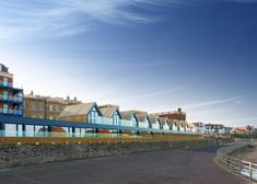 This row of beach houses in Margate features pitched roofs intended to resemble traditional beach huts and fully glazed gable ends.