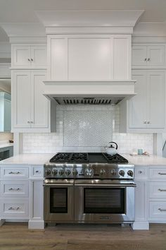 White shaker kitchen cabinets fitted with polished nickel hardware and white marble countertops flank a Thermador dual range positioned on sawn oak wood floors below a white paneled hood fixed on white subway tiles framing marble herringbone cooktop tiles.