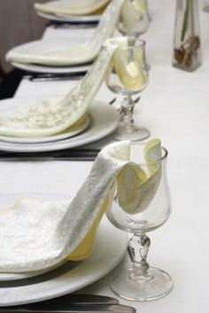 wedding napkins draped from glasses to plate in an elegant display