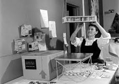 Ray Eames with a model of the original proposal for the Eames House, the bridge house, designed by Charles Eames and Eero Saarinen