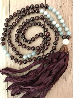 Gorgeous Aquamarine beads are paired with the rich tones of Garnet to make this 108 hand-knotted mala necklace. Gorgeous plum hand-dyed Sari Silk tassel is topped with a large Moonstone guru bead. This mala was inspired by one of my lovely and loyal customers as a custom listing for her. It