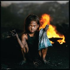 Searching for usable materials in the charcoal fields and rubbish tips is this little Filipino girl.