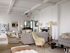 The architects complemented the client's art collection with a mix of vintage French and Scandinavian pieces, as well as custom designs. In the living room, the firm grouped 1930s Paul Dupré-Lafon floor lamps from Galerie L'Arc en Seine and circa-1965 Jacques Quinet end tables from Galerie Arcanes with seating by Jonas; the mobile is by Alexander Calder. The armchair in the foreground is a '50s design by Kerstin Hörlin-Holmquist, and the low table is by Jean Royère; the rugs were custom made…