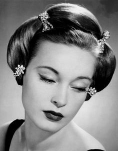 Black & white photo of pretty young woman with special hairdo. Costume jewellery advertisement, 1953
