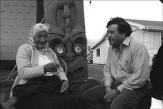 Tukaki wharenui, Te Kaha-nui-a-tiki marae. June 1973 Local kuia Kiritahanga Poihipi and Hone Tuwhare outside the Tukaki wharenui. Image by John Miller. Nz History, John Miller, New Zealand, The Outsiders, June, Image, People, Folk