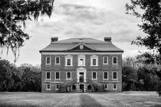 Black and white photograph of the front exterior of Drayton Hall, nine miles outside Charleston. Drayton Hall was built about 1740, and is the only South Carolina plantation home to survive the Revolutionary War and the Civil War intact. The house is now held in a state of preservation, maintained but not restored, which means that original paint, woodwork, and carved ceilings can still be seen. Archival Pigment Prints on Fine Art Paper (Standard): - Printed on professional quality…