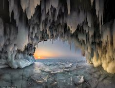 Russian photographer Andrey Grachev risked his life on the frozen lake to capture breathtaking images of the ice cave at sunrise