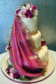 A strikingly gorgeous fondant drape inspired by the exotic beauty of an Indian sari adorns this fabulous wedding cake by Rosebud Cakes in Beverly Hills, California.....