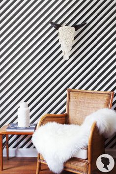 Friday eye candy! Black and white Livettes diagonal stripe pattern wallpaper with exellent interior accents: fantastic carvedskulls decor and snow white sheepskin. :)