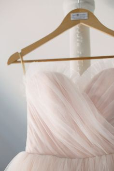 Blush Pink Tulle Wedding Dress - Vintage Style Ball Gown - Kristine Style - Avail & Company, LLC  This pale pink dress is simple and elegant with a poofy tulle skirt out of a fairytale. The dress also has detachable straps and a ruffled tulle trim. It is perfect for multiple venues. Indoors and outdoors.