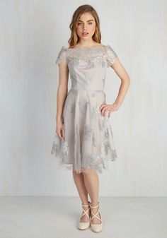 With your hair styled and makeup perfected, you slip into this silver dress before floating off to the fete. A gorgeous creation from Eva Franco, this short-sleeved stunner features a richly-detailed illusion neckline and embroidered flowers atop its mesh overlay - perfect for all the elegance that awaits you!