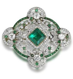A Belle Époque emerald and diamond brooch/pendant, circa 1910. Set to the centre with a square-cut emerald and single-cut diamond cluster, to an openwork border set with swags and floral garlands, within a quatrefoil frame, millegrain-set throughout with single and brilliant-cut diamonds and calibré and circular-cut emeralds, diamonds approximately 4.80 carats total, detachable brooch fitting. #BelleEpoque #Pendant  #brooch