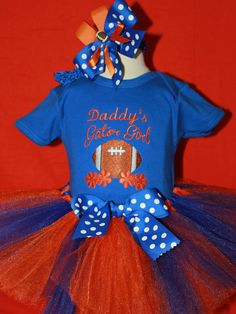 Daddy will be so proud of his little baby Gator girl in this cute outfit. This royal blue bodysuit is embroidered. The outfit comes with a very full orange and blue ribbon tie tutu. The set also comes with a matching headband. If you would like I can change the bodysuit to say Mommy's, or anyone else on it. Just tell me in the notes on the order if you want the bodysuit to say something different. It will be a blue t shirt instead of a bodysuit for older girls. | Shop this product here…