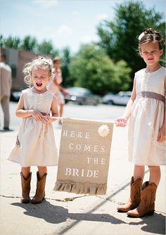 Flower girls with cowboy boots.  How adorable is this?  I think the sign is a bit much, but they are too cute.
