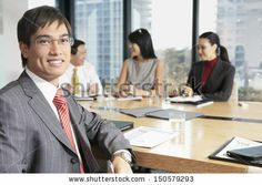 Portrait of confident young Asian businessman with colleague in boardroom by bikeriderlondon, via ShutterStock