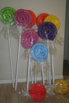 Giant lollipops for Ara's Wizard Oz Party made of swimming pool noodles @ dollar store and pvc piping. The ones on floor are made of paper lanterns wrapped and twisted at ends.