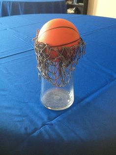 Basketball centerpieces  Bought little squishy basketballs at the dollar store, netting from hobby lobby, and vases from good will. Cut the net and hot glue it to the vase!