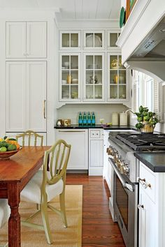 Fab and Functional Kitchen - Our New Favorite 800-Square-Foot Cottage That You Can Have Too  - Southernliving. Pushing the classically styled white cabinets and soapstone countertops along the walls maxes out floorspace in the tiny cooking area and meshes well with the rest of the living room's decor. Glass-front upper cabinets offer a more refined (and nearly as airy) option than traditional open shelving that is typically found in rural kitchens. A shiplap backsplash and old-timey louvered…