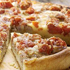 "Chicago-style Deep Dish Pizza - Did you ever wonder about the ""pie"" in pizza pie? This dish will make that connection clear for you. With its 1 1/2"" tall crust cradling distinct layers of cheese, sausage, and tomatoes, this is definitely a knife-and-fork pizza PIE."