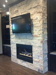 Stacked stone. I don't like tv over fireplace but this is okay with the cabinets on the side.  Maybe an idea