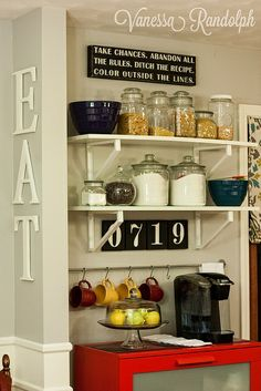 Shelves in gray with these brackets in silver on either side of mirror. Put the flour and sugar in big mason jars. Coffee mugs on one shelf.