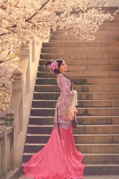 Woman wearing pink & purple standing next to stairs