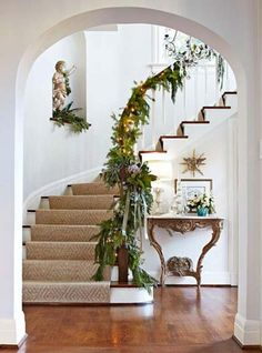Curved staircase with wall niche and window light. All decked out with Xmas greenery.