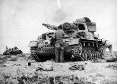 British soldiers examine wrecked German tanks Pz.Kpfw. IV (foreground — Pz.Kpfw. IV Ausf E).